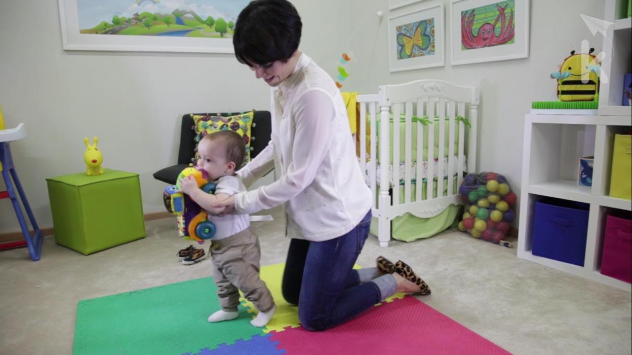 baby learning to balance taking first steps